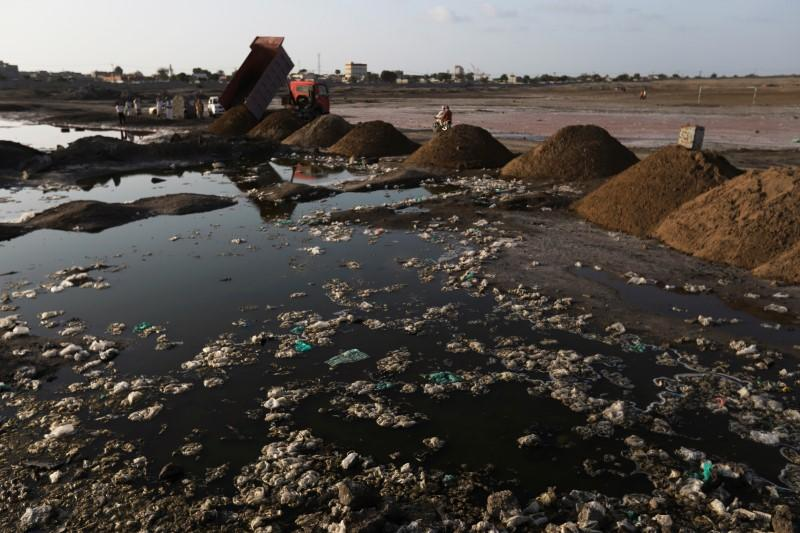 Truck pours sand on stagnant water pools to drain the potential breeding sites of Aedes aegypti mosquitoes, known to spread the dengue fever, in Hodeidah