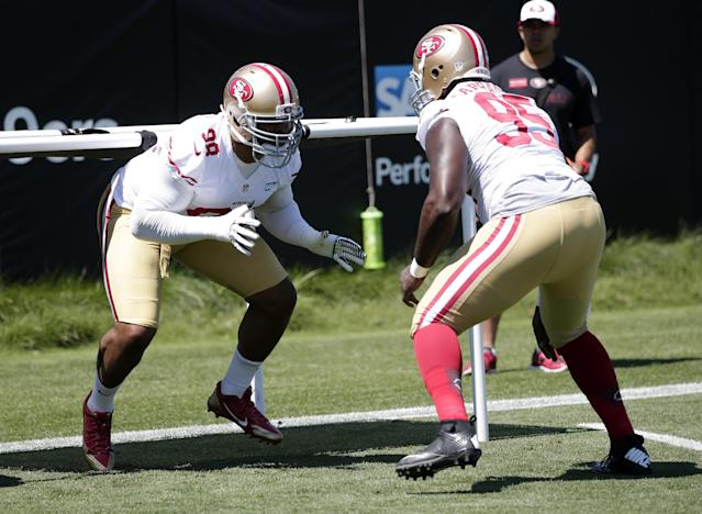 San Francisco 49ers lineman Lawrence Okoye, left, runs a drill with teammate Tank Carradine (95) during an NFL football training camp on Thursday, July 24, 2014, in Santa Clara, Calif. (AP Photo)