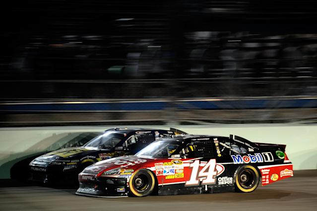 HOMESTEAD, FL - NOVEMBER 20: Tony Stewart, driver of the #14 Office Depot/Mobil 1 Chevrolet, drives alongside A.J. Allmendinger, driver of the #43 Best Buy Ford, during the NASCAR Sprint Cup Series Ford 400 at Homestead-Miami Speedway on November 20, 2011 in Homestead, Florida. (Photo by Jared C. Tilton/Getty Images)