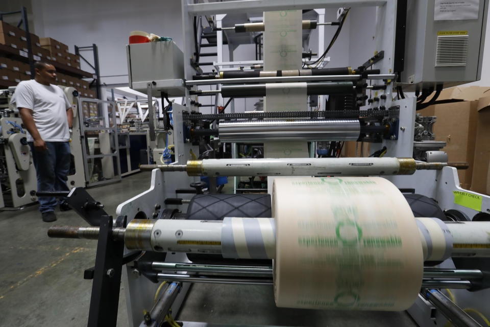 In this Friday, July 5, 2019, photo Andre Harris works on the line at beyond Green, a maker of biodegradable bags in Lake Forest, Calif. (AP Photo/Chris Carlson)