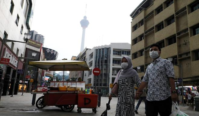 A couple wearing protective face masks cross a street, following the outbreak of the coronavirus in Kuala Lumpur, Malaysia. Photo: Reuters