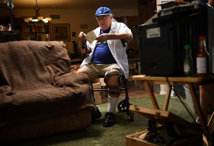 "Conrad Munatones goes through old photos at his home in San Dimas. He fondly remembers the days when baseball in the barrio ""was quite a thing."" <span class=""copyright"">(Wally Skalij / Los Angeles Times)</span>"