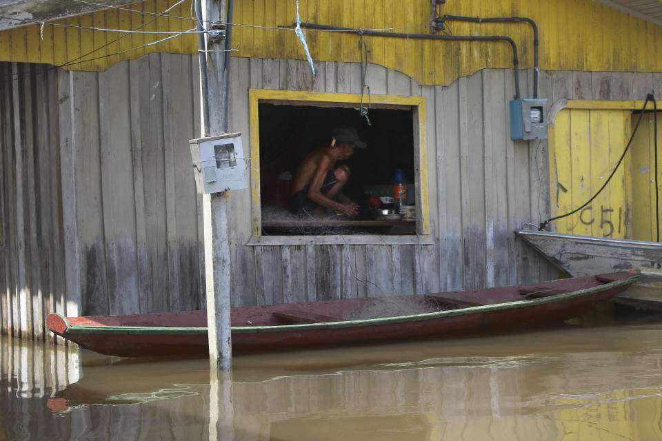 A resident crouches on a raised floor set up inside a home to stay above floodwaters in Anama, Amazonas state, Brazil, Thursday, May 13, 2021. (AP Photo/Edmar Barros)