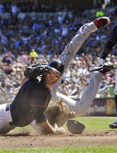 Texas Rangers pitcher Yu Darvish gets flipped in a collision with Minnesota Twins' Ryan Doumit, left, as he  tagged Doumit who attempted to score on a runner's fielders choice in the fourth inning of a baseball game Saturday, April 14, 2012, in Minneapolis. (AP Photo/Jim Mone)