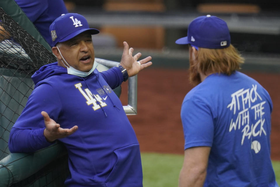 Los Angeles Dodgers manager Dave Roberts talks with third baseman Justin Turner during batting practice before Game 2 of the baseball World Series against the Tampa Bay Rays Wednesday, Oct. 21, 2020, in Arlington, Texas. (AP Photo/Sue Ogrocki)