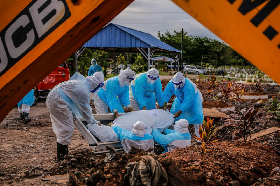 Workers in personal protective equipment bury the body of a Covid-19 victim at the Muslim cemetery in Section 21, Shah Alam, July 10, 2021. ― Picture by Hari Anggara