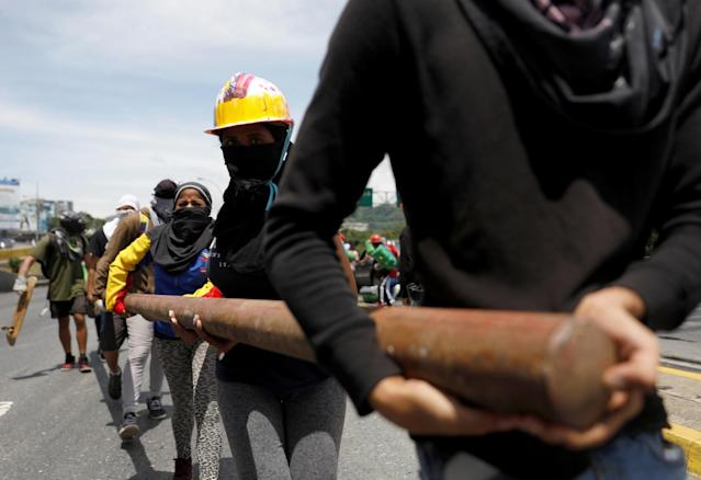<p>Opposition supporters carry materials to build a barricade to block an avenue while rallying against President Nicolas Maduro in Caracas, Venezuela, May 15, 2017. (Carlos Garcia Rawlins/Reuters) </p>