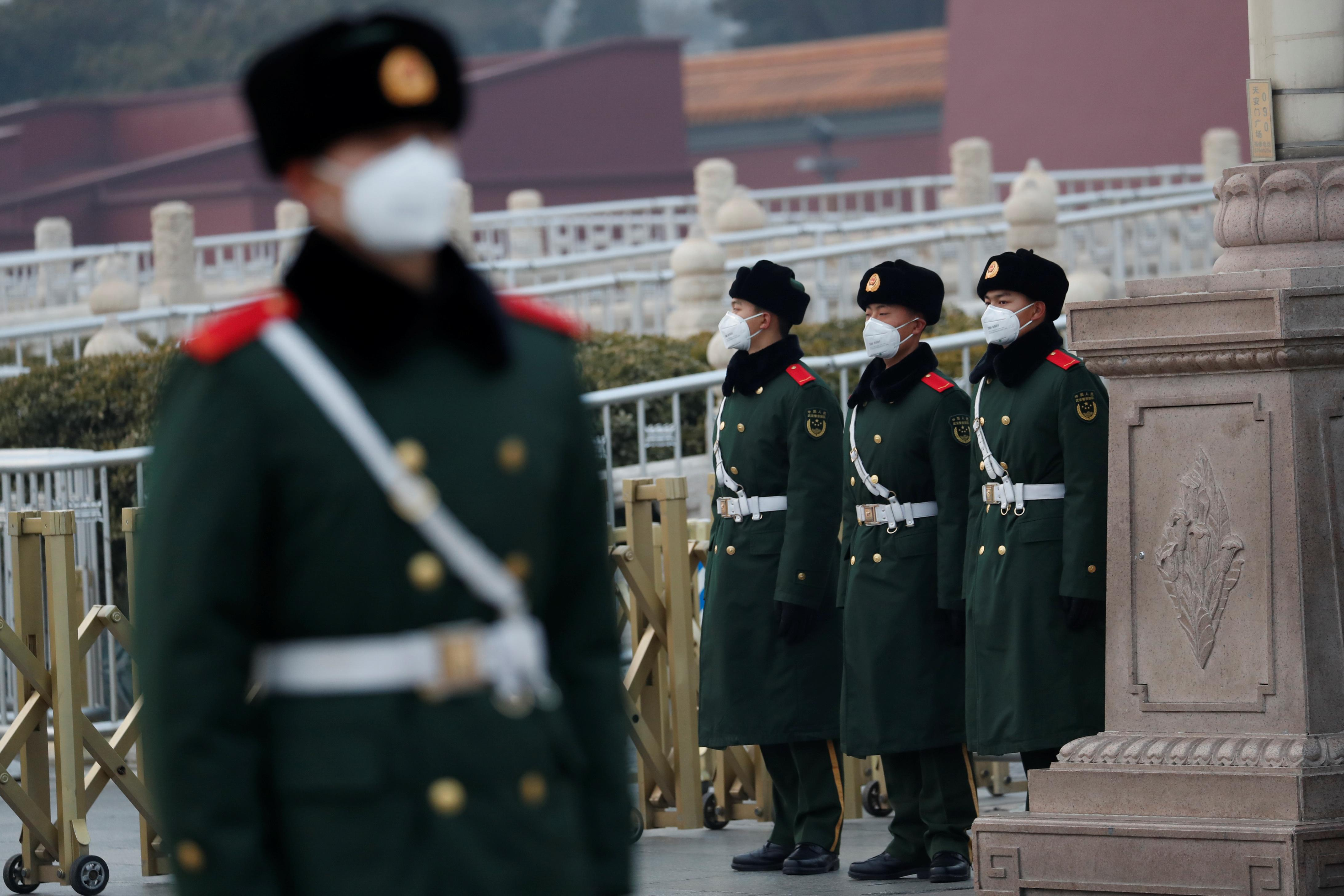 Paramilitary officers wearing face masks stand guard at the Tiananmen Gate, as the country is hit by an outbreak of the new coronavirus, in Beijing, China January 27, 2020. REUTERS/Carlos Garcia Rawlins