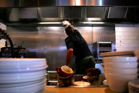 A cook from Brazil, identified only as Francisco, who says he will be applying for an Australian work permit known as a 457 visa, works in the kitchen of a cafe in Sydney, Australia