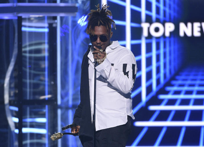 """FILE - In this May 1, 2019 file photo, Juice WRLD accepts the award for top new artist at the Billboard Music Awards at the MGM Grand Garden Arena in Las Vegas. The Chicago-area rapper, whose real name is Jarad A. Higgins, was pronounced dead Sunday, Dec. 8 after a """"medical emergency'' at Chicago's Midway International Airport, according to authorities. Chicago police said they're conducting a death investigation. (Photo by Chris Pizzello/Invision/AP, File)"""