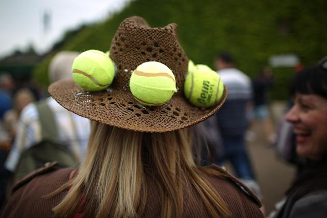 LONDON, ENGLAND - JUNE 27: A spectator wears tennis balls in her hat on day four of the Wimbledon Lawn Tennis Championships at the All England Lawn Tennis and Croquet Club on June 27, 2013 in London, England. Play has been disrupted on some courts due to rain. (Photo by Peter Macdiarmid/Getty Images)