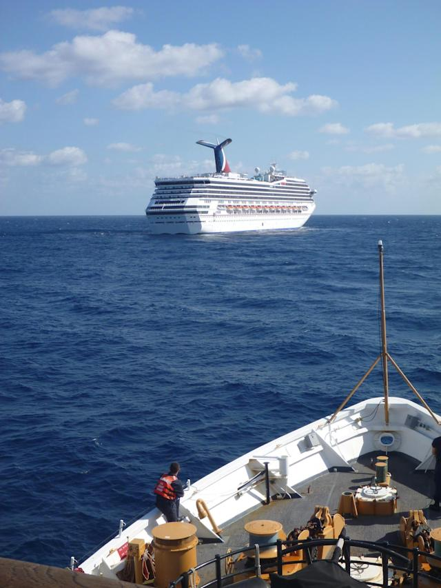 In this image released by the U.S. Coast Guard on Feb. 11, 2013, the Coast Guard Cutter Vigorous patrols near the cruise ship Carnival Triumph in the Gulf of Mexico, Feb. 11, 2013. The Carnival Triumph has been floating aimlessly about 150 miles off the Yucatan Peninsula since a fire erupted in the aft engine room early Sunday, knocking out the ship's propulsion system. No one was injured and the fire was extinguished. (AP Photo/U.S. Coast Guard- Lt. Cmdr. Paul McConnell)