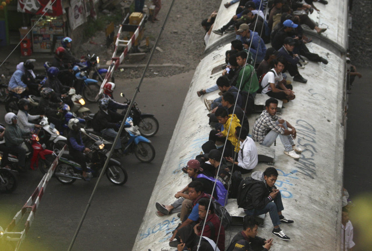 People ride on top of a commuter train in Jakarta, Indonesia, Tuesday, Jan. 17, 2012. Indonesia has gone to imaginative extremes to try to stop commuters from illegally riding the roofs of trains, hosing down the scofflaws with red paint, threatening them with dogs and appealing for help from religious leaders. Now the authorities have an intimidating and possibly even deadly new tactic: Suspending rows of grapefruit-sized concrete balls to rake over the top of trains as they pull out of stations, or when they go through rail crossings. (AP Photo/Dita Alangkara)