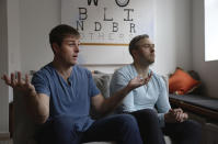 Brothers, Bryan, left, and Bradford Manning, discuss the origins of their clothing company, Two Blind Brothers, in their New York City loft on Friday, Oct. 23, 2020. The brothers who've lost much of their vision to a rare degenerative eye disorder began their company in 2016 and have donated all profits, more than $700,000, to preclinical research trials to help cure blindness. (AP Photo/Jessie Wardarski)