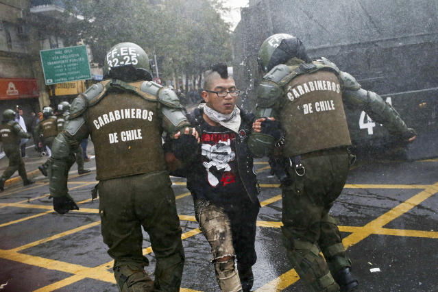 <p>A student is detained by police after throwing an object at them during a protest march demanding the government overhaul the education funding system that would include canceling their student loan debt, in Santiago, Chile, May 9, 2017. Some students stay in debt for up to 20 years after completing their studies. (AP Photo/Esteban Felix) </p>