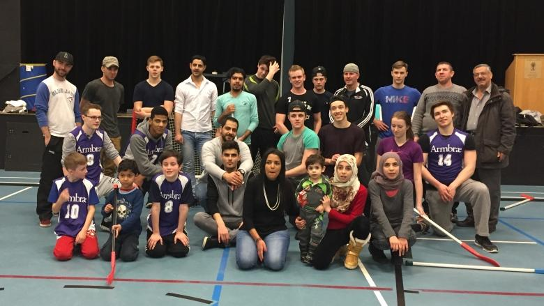 Teens teach Syrian refugees how to play floor hockey