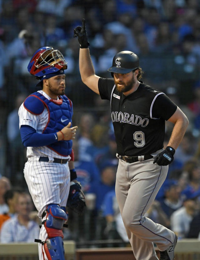 Colorado Rockies' Daniel Murphy right, celebrates at home plate after hitting a solo home run while Chicago Cubs catcher Victor Caratini left, looks on during the fourth inning of a baseball game Tuesday, June 4, 2019, in Chicago. (AP Photo/Paul Beaty)