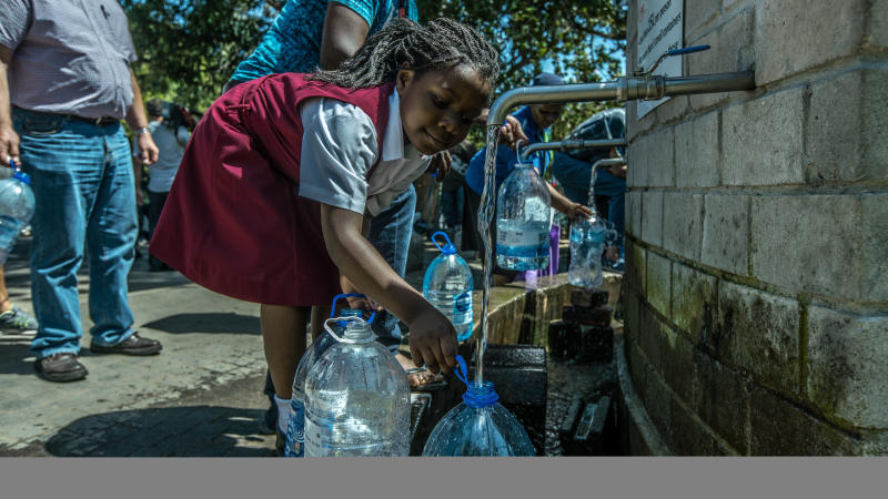 Cape Town residents queue to refill water bottles on Jan. 30, 2018. Diminishing water supplies may soon lead to the taps being turned off for the four million inhabitants of Cape Town. (Morgana Wingard via Getty Images)