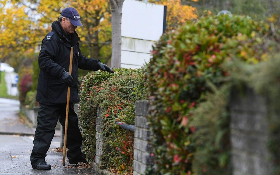 Police officers search bushes at the scene for evidence - Kirsty O'Connor/PA