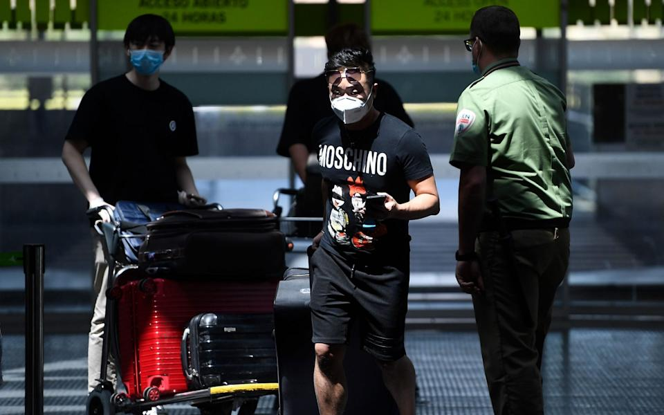 AFP - Passengers wearing face masks head to their boarding gate at the Barajas airport in Madrid, a day before the country's state of emergency ends following a national lockdown to stop the spread of the coronavirus./AFP