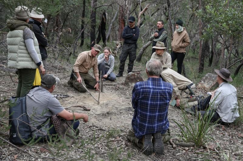 A wilderness survival instructor teaches students during a basic skills course in northern Sydney