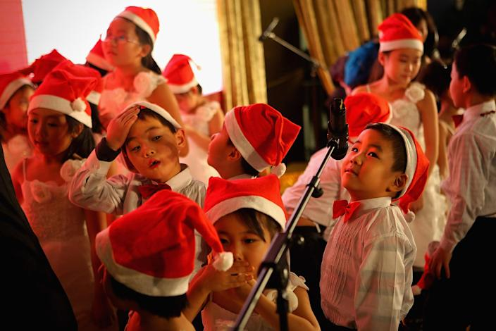 BEIJING, CHINA - DECEMBER 24: Chinese children rest after singing Christmas songs for customers at a shopping center on Christmas Eve December 24, 2011 in Beijing, China. Though Christmas is not officially celebrated in China, the holiday is becoming increasingly popular as Chinese adopt more Western ideas and festivals. (Photo by Feng Li/Getty Images)