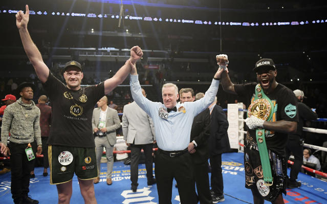 Tyson Fury poses with Deontay Wilder along with referee Jack Reiss after their WBC heavyweight championship boxing match ended in a draw, Saturday, Dec. 1, 2018, in Los Angeles. (AP Photo/Mark J. Terrill)