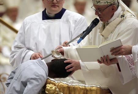 Pope Francis baptizes a young boy during the Easter vigil mass in Saint Peter's basilica at the Vatican