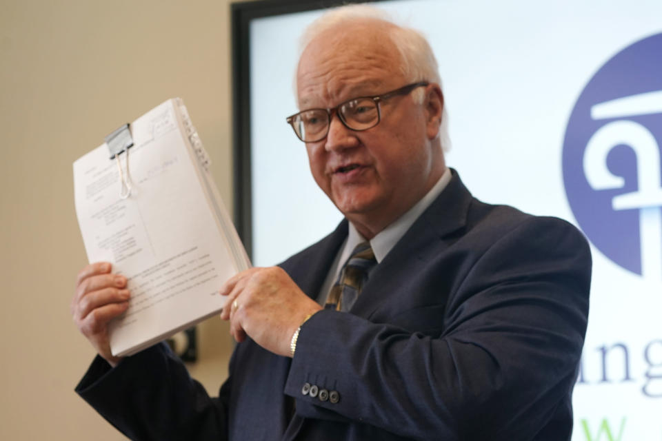 Jim Davids, of the Founding Freedom Law Center, holds a copy of a lawsuit during a news conference at the foundation offices in Richmond, Va., Tuesday, March 30, 2021. Davids announced the filing of a lawsuit challenging the state Department of Education's newly issued guidelines on the treatment of transgender students. (AP Photo/Steve Helber)
