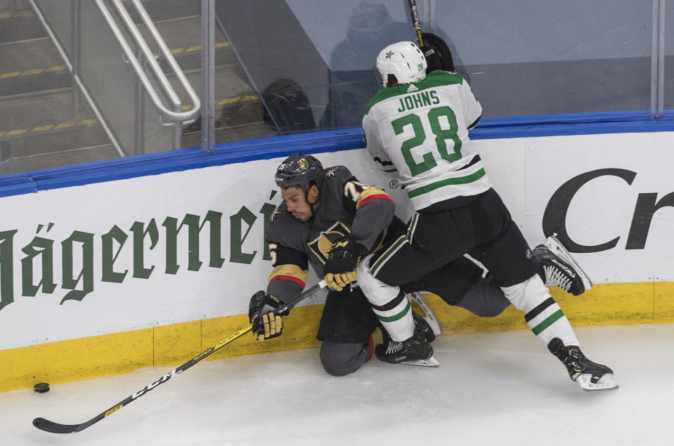 Dallas Stars' Stephen Johns (28) checks Vegas Golden Knights' Ryan Reaves (75) during the third period of an NHL hockey playoff game Monday, Aug. 3, 2020, in Edmonton, Alberta. (Jason Franson/The Canadian Press via AP)