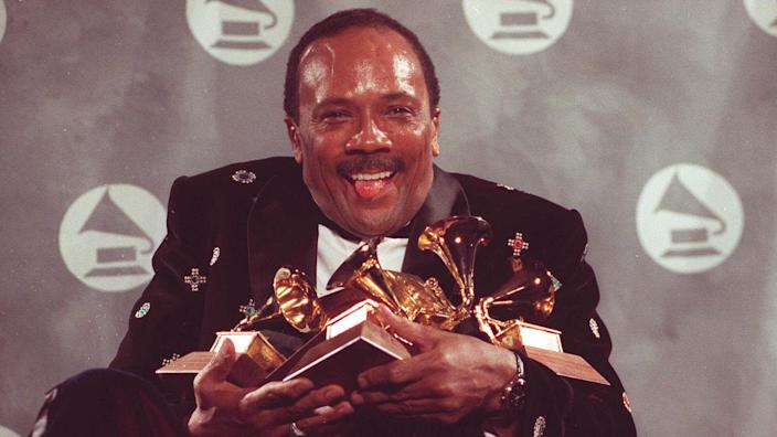 Quincy Jones cradles his Grammy awards,including the album of the year award, for his eclectic album