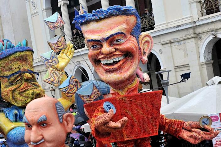 An effigy of new Greek Prime Minister Alexis Tsipras, holding a one Euro coin in one hand and a Drachma, the former currency, in the other, is paraded at the Patras carnival, west of Athens, on February 22, 2015 (AFP Photo/Giota Korbaki)