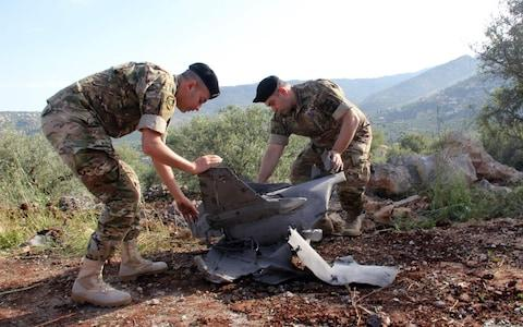 Lebanese soldiers inspect remains of a surface to air missile that landed in the southern Lebanon after being fired by Iranian forces from Syria on the Israeli-occupied Golan - Credit: AFP
