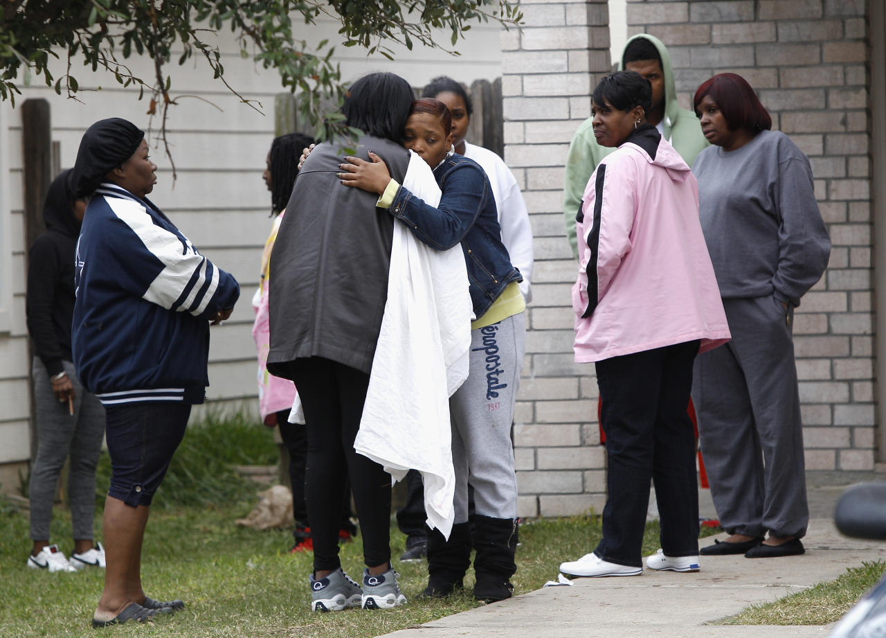 Family and friends console each other outside 7318 Enchanted Creek in Cypress, Texas, Sunday, Nov. 10, 2013, after two people were killed and at least 22 others were injured Saturday night when gunfire rang out at a large house party in a Houston suburb, sending partygoers fleeing in panic, authorities said. Authorities say they're seeking two gunmen. (AP Photo/Bob Levey)