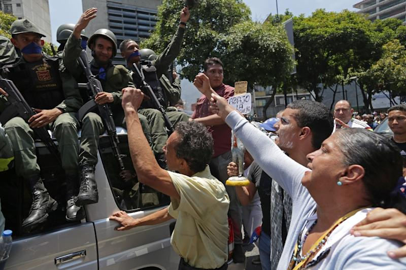 National Guard members who joined Venezuela's self-proclaimed acting president Juan Guaido in his campaign to oust President Nicolas Maduro, are greeted by opposition supporters in Caracas on April 30, 2019 (AFP Photo/Cristian HERNANDEZ)