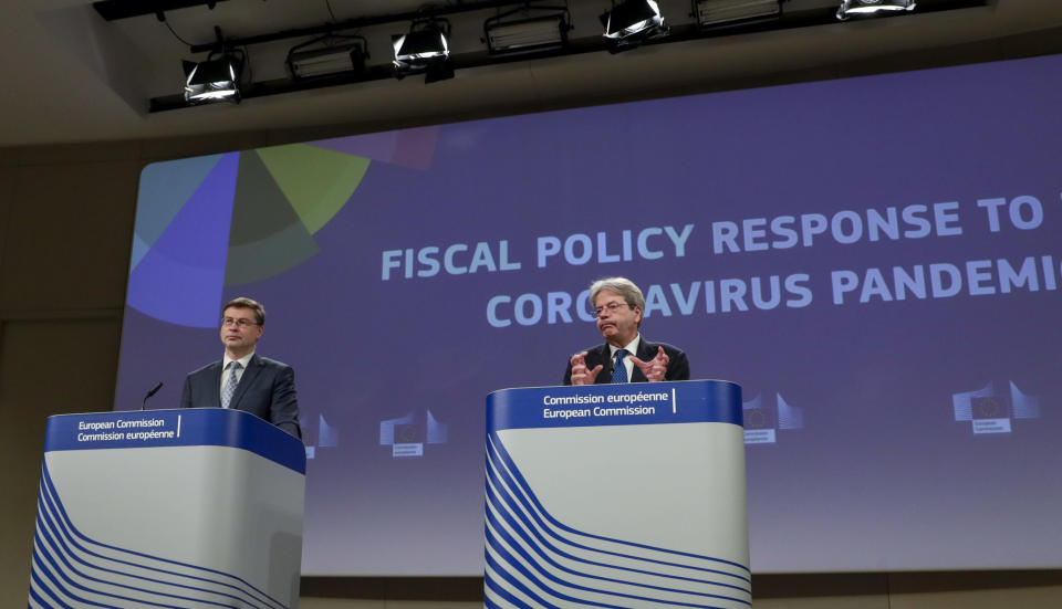 European Commissioner for Economy Paolo Gentiloni, right, and European Commissioner for an Economy that Works for the People Valdis Dombrovskis, participate in a media conference on the Fiscal Policy Response to the Coronavirus Pandemic at EU headquarters in Brussels, Wednesday, March 3, 2021. (Olivier Hoslet, Pool via AP)