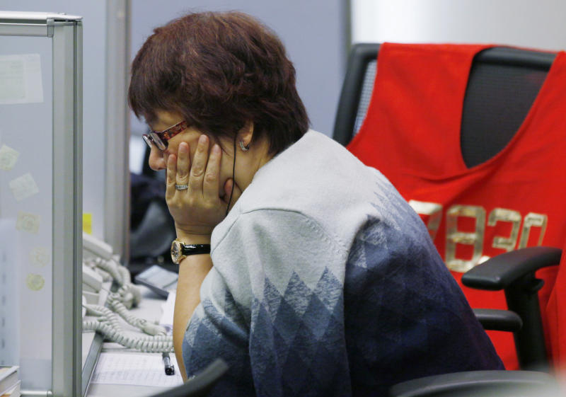 A floor trader studies stock price at the Hong Kong Stock Exchange Friday, May 11, 2012. Asian stock markets were lower Friday as traders eyed political upheaval in Greece and signs of slowing economic growth in China. Hong Kong's Hang Seng fell 1.2 percent to 19,989.54. (AP Photo/Kin Cheung)