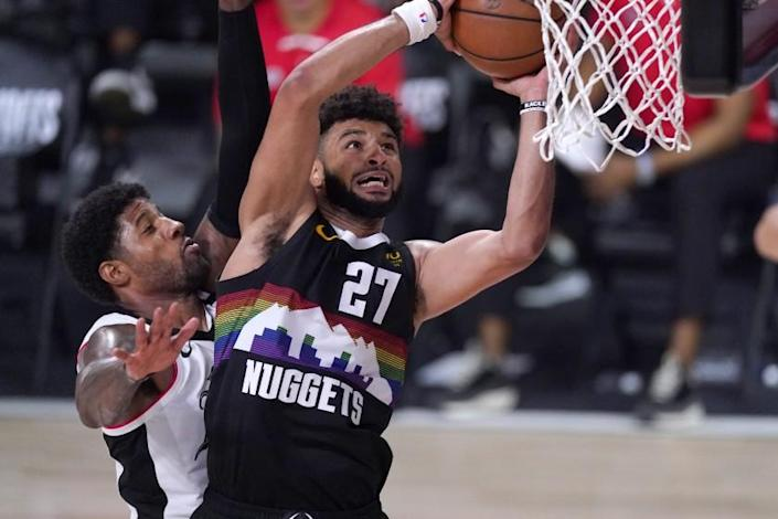 """Nuggets guard Jamal Murray goes up for a shot as Clippers forward Paul George defends during the second half on Sunday in Orlando, Fla. <span class=""""copyright"""">(Mark J. Terrill / Associated Press)</span>"""