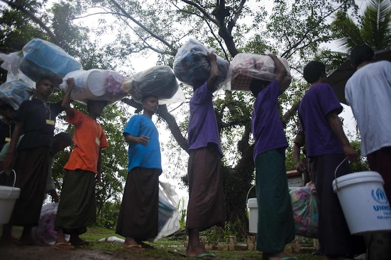 Migrants who were found at sea on a boat stand in line as they are repatriated across the Myanmar-Bangladesh border in Rakhine in June 2015 (AFP Photo/Ye Aung Thu)