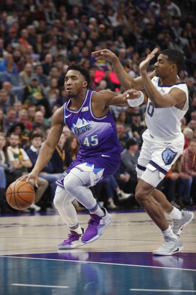 Utah Jazz guard Donovan Mitchell (45) drives past Memphis Grizzlies guard De'Anthony Melton (0) during the first half, during an NBA basketball game Saturday, Dec. 7, 2019, in Salt Lake City. (AP Photo/George Frey)