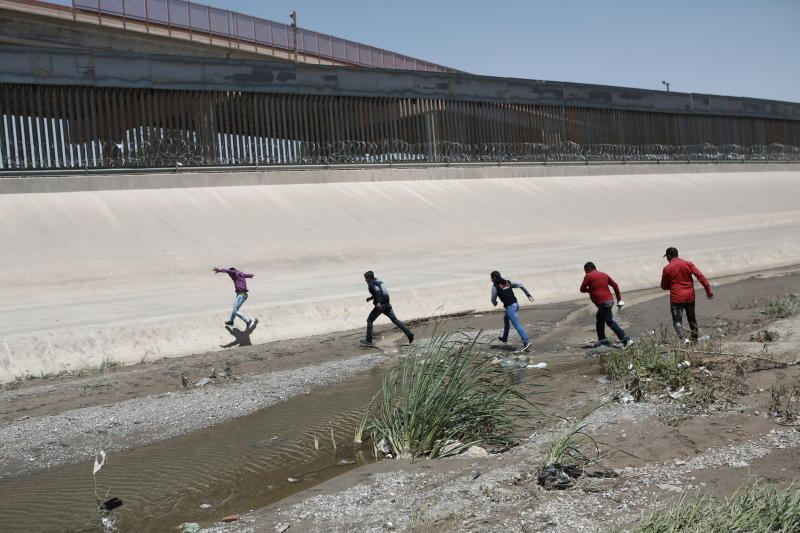 FILE - In this June 15, 2019, file photo, migrants cross the Rio Bravo illegally to surrender to the American authorities, on the U.S.-Mexico border between Ciudad Juarez and El Paso. Hundreds of thousands of people have been arriving at the border in recent months, many of them families fleeing violence and poverty in Central America. Once they reach the border, they can take different paths to try to get into the U.S. (AP Photo/Christian Torres, File)