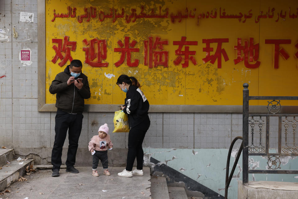 A family stands at the entrance to an underground retail street in Aksu in western China's Xinjiang Uyghur Autonomous Region on March 18, 2021. China is going global with its campaign to deflect criticism over its policies in the northwestern region of Xinjiang. The region's government on Wednesday, June 2, organized a transcontinental zoom call showcasing economic development and poverty elimination. (AP Photo/Ng Han Guan)