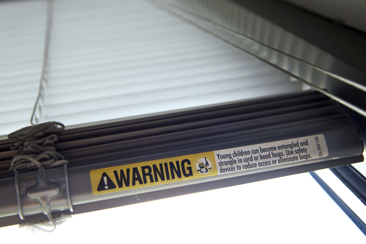 FILE - This Wednesday, May 6, 2015 file photo shows a warning label of strangulation risks from mini blind cords in Washington. According to a study released on Monday, Dec. 11, 2017, children's injuries and deaths from window blinds have not stalled despite decades of safety concerns. (AP Photo/Jacquelyn Martin)