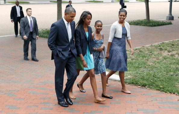 U.S. President Barack Obama, Malia Obama, Sasha Obama, and first lady Michelle Obama walk from the White House to St. John's Episcopal Church August 19, 2012 in Washington, DC. Obama is embroiled in an election race with Republican presidential candidate, former Massachusetts Gov. Mitt Romney. (Photo by Dennis Brack-Pool/Getty Images)