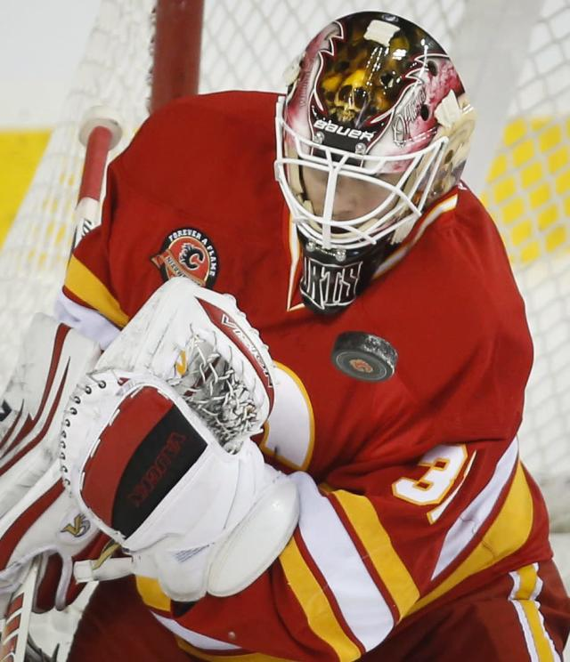 Calgary Flames goalie Joni Ortio, from Finland, bobbles the puck during the first period of an NHL hockey game against the New York Islanders on Friday, March 7, 2014, in Calgary, Alberta. (AP Photo/The Canadian Press, Jeff McIntosh)