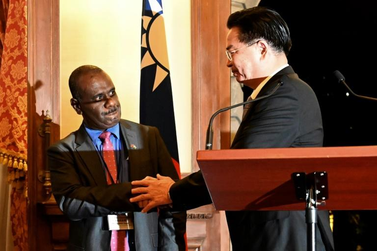 Taiwan Foreign Minister Joseph Wu shakes hands with Solomon Islands' Foreign Minister Jeremiah Manele during a press conference in Taipei. The Solomon Islands is mulling scrapping diplomatic links with Taipei in favour of Beijing (AFP Photo/Sam YEH)