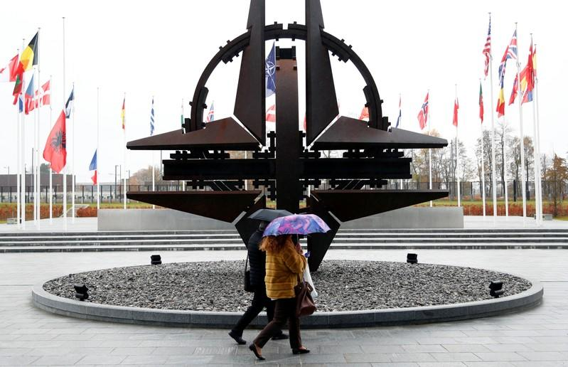 People hold umbrellas outside NATO headquarters in Brussels