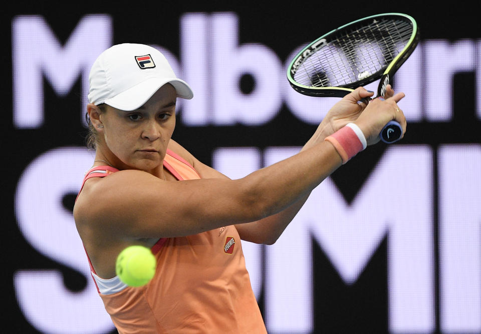 FILE - In this Tuesday, Feb. 2, 2021 file photo, Australia's Ash Barty makes a backhand return to Romania's Ana Bogdan during a tuneup tournament ahead of the Australian Open tennis championships in Melbourne, Australia. No. 1 Ash Barty – Won her first Grand Slam title at the 2019 French Open but sat out most of last year because of the pandemic. (AP Photo/Andrew Brownbill, File)
