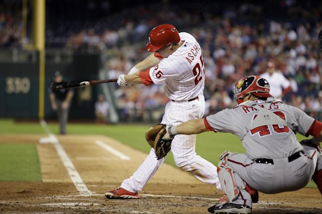 Philadelphia Phillies' Cody Asche follows through after hitting a two-run single off Washington Nationals starting pitcher Gio Gonzalez during the fourth inning of a baseball game, Tuesday, Sept. 3, 2013, in Philadelphia. At right is Wilson Ramos. (AP Photo/Matt Slocum)