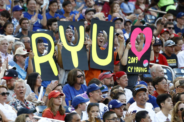 Fans hold signs for Los Angeles Dodgers starting pitcher Hyun-Jin Ryu, of South Korea, in the first inning of a baseball game between the Dodgers and the Washington Nationals, Friday, July 26, 2019, in Washington. (AP Photo/Patrick Semansky)